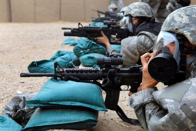 soldiers aiming weapons on sandbags